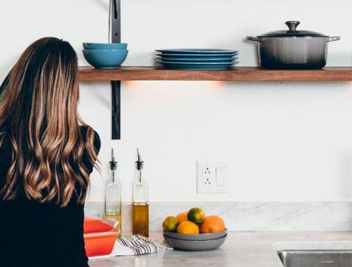 Brunette woman in brightly lit kitchen preparing food